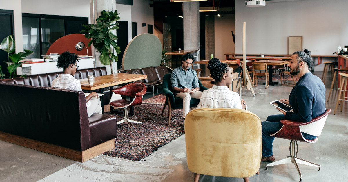 Kolleger snakker sammen i et uformelt rom på jobb..
