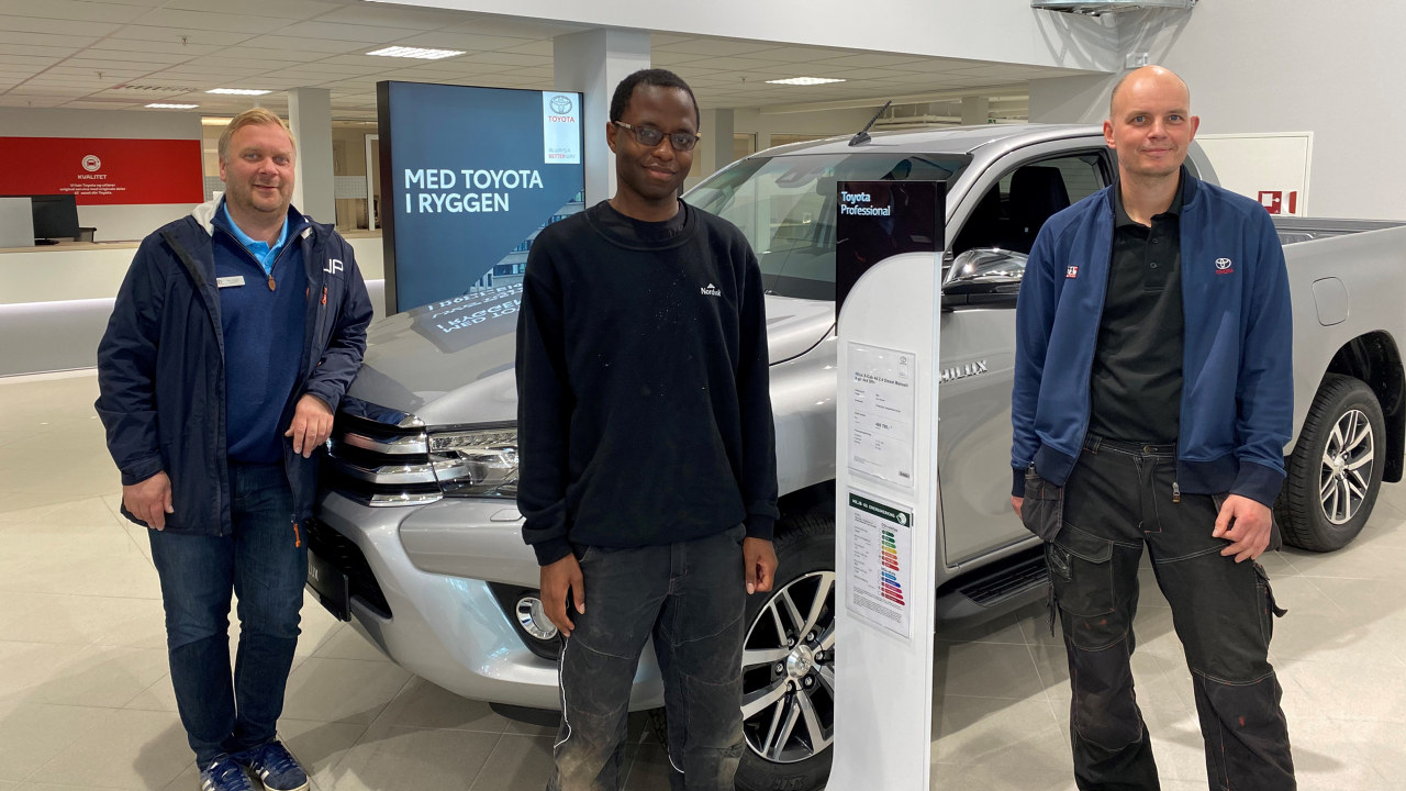 Mark-Anthony Atepo i Toyota-butikken sammen med salgssjefTom Fossen (t.v) og teknisk leder Gøran Skogstad (t.h).